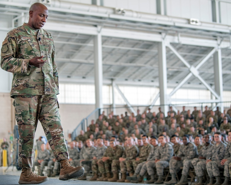 Chief Master Mgt. of the Air Force Kaltheth O. Wright stands in front of and talks to U.S. Airmen sitting in bleachers.