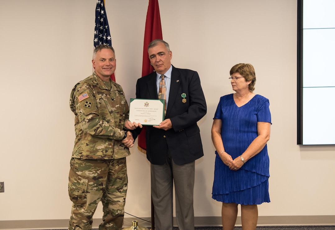 COL Philip Secrist, TAM Commander, hands Mike Graham his certificate of retirement while Mike's wife Shannon looks on. Mike completed 41 years of federal service including 10 as an Army engineer, 28 Sep. 2019.