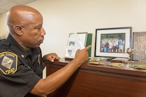 Deputy Chief Boris A. Robinson, Marine Corps Police Department, MCLB Barstow, points out the photo he took with former President George W. Bush, when he was attending the FBI Academy at Quantico, Virginia. The former president had been conducting his workout with Secret Service Agents in attendance when he stopped to say hello to the FBI agents.