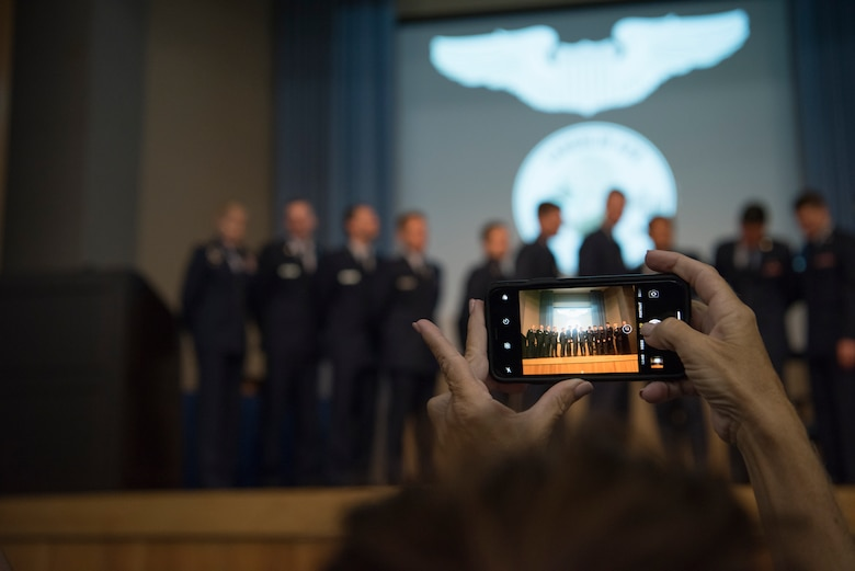 An attendee of Specialized Undergraduate Pilot Training class 19-25's graduation ceremony takes a group picture at Laughlin Air Force Base, Texas, Spet. 27, 2019. Maj. Gen. Jeannie Leavitt, Air Force Recruiting Service commander, was the guest speaker at the ceremony, handing off wisdom to the newly pinned pilots. (U.S. Air Force photo by Staff Sgt. Benjamin N. Valmoja)