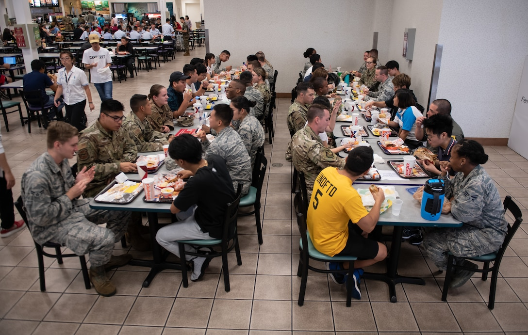 U.S. Air Force Airmen eat lunch with college students during Air Force Immersion Day Sept. 23, 2019, at Kadena Air Base, Japan. Air Force Immersion Day is a new community engagement program hosted by the base to teach college and vocational students about the 18th Wing's mission. The luncheon enabled students to practice English and learn about Airmen's jobs, families and experiences. (U.S. Air Force photo by Staff Sgt. Micaiah Anthony)