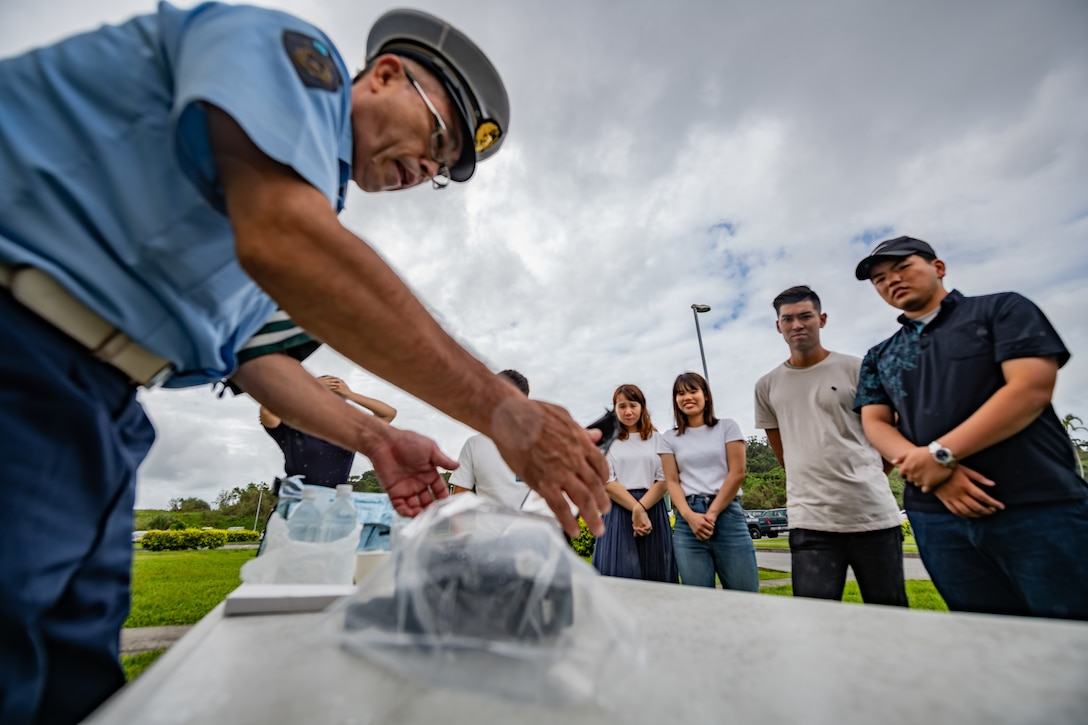 An Okinawa Prefectural Police officer shows students how they collect breathalyzer samples during Air Force Immersion Day, Sept. 23, 2019, at Kadena Air Base, Japan. The 18th Security Forces Squadron teamed up with the police to educate local students about their bilateral partnership and combined effort to combat and reduce intoxicated drivers on island. (U.S. Air Force photo by Staff Sgt. Micaiah Anthony)