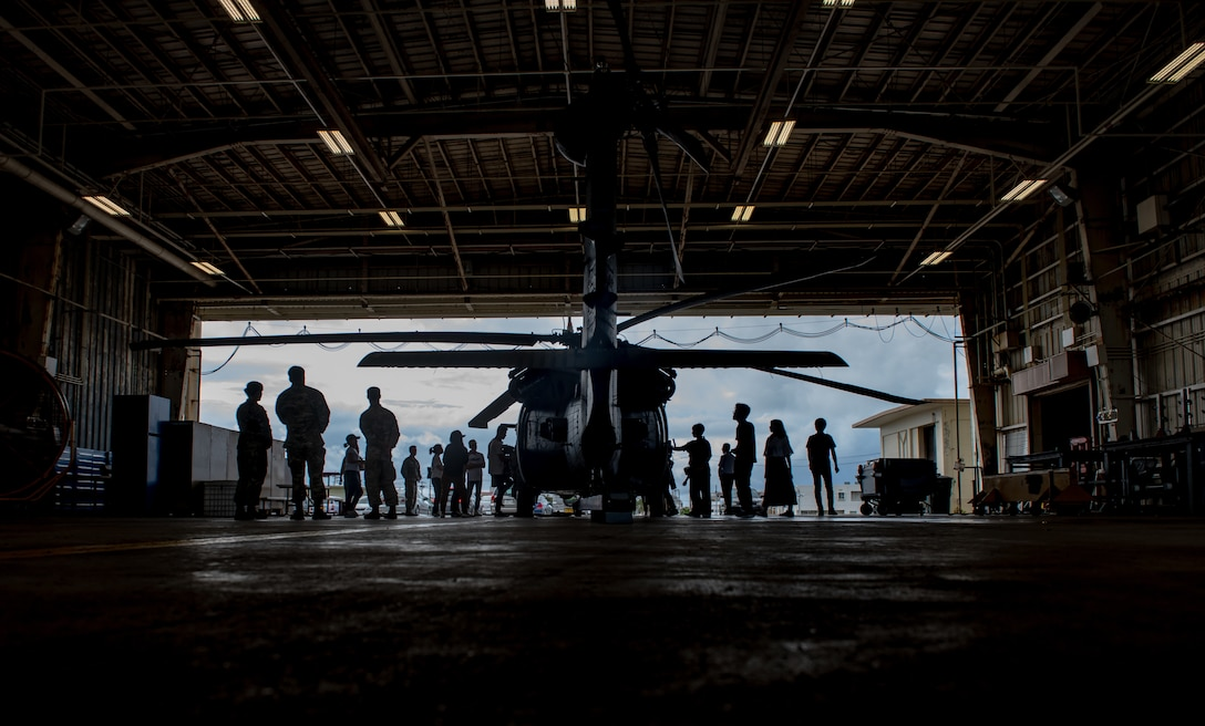 Students look at a U.S. Air Force HH-60G Pave Hawk assigned to the 33rd Rescue Squadron during Air Force Immersion Day, Sept. 23, 2019, at Kadena Air Base, Japan. During the tour, students learned about the unit's role in supporting Airmen from the 31st Rescue Squadron in personnel recovery, humanitarian aid, disaster relief and tactical combat casualty care. (U.S. Air Force photo by Staff Sgt. Micaiah Anthony)