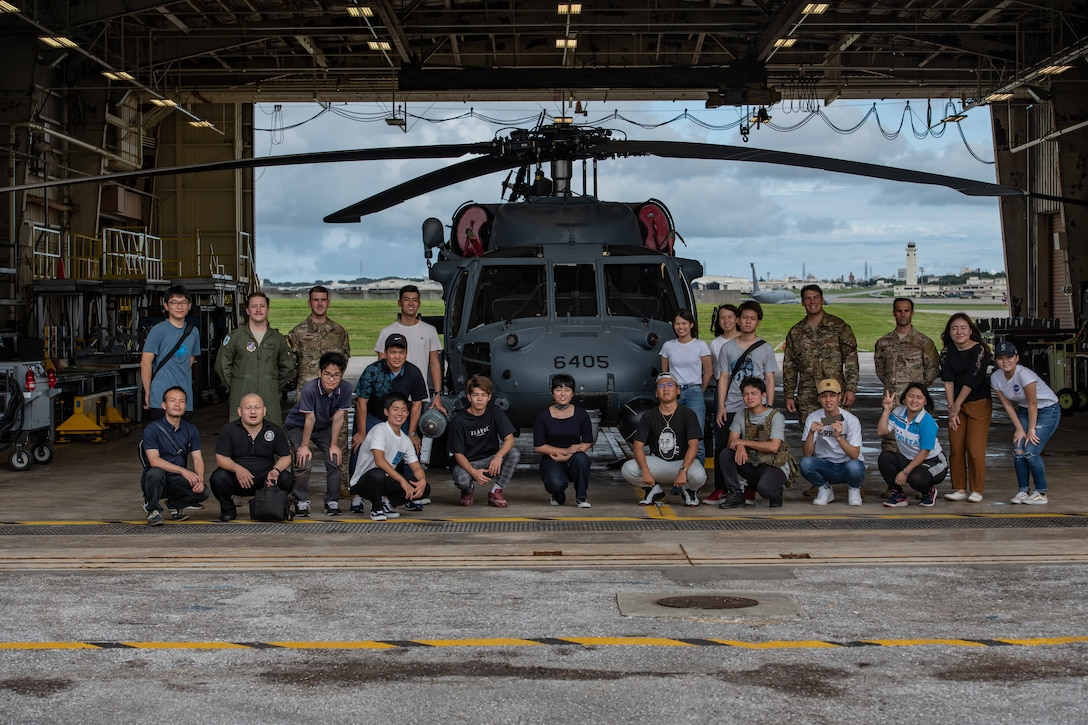 U.S. Air Force Airmen from the 31st and 33rd Rescue Squadrons pose for a photo with local students during Air Force Immersion Day, Sept. 23, 2019, at Kadena Air Base, Japan. Team Kadena invited 18 local university and vocational students to the base to participate in the interactive tour. (U.S. Air Force photo by Staff Sgt. Micaiah Anthony)