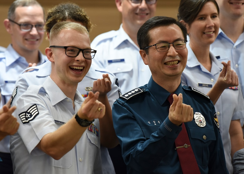 Sang-joon Lim, Gunsan Korean National Police chief, creates the hand heart symbol along with Staff Sgt. Andrew Clemenson, U.S. Air Force Band of the Pacific drummer, and other band members in Gunsan City, Republic of Korea, Sept. 24, 2019. The bands mission is to reinforce alliances, expand partnerships and build cross-cultural trust. (U.S. Air Force photo by Staff Sgt. Anthony Hetlage)