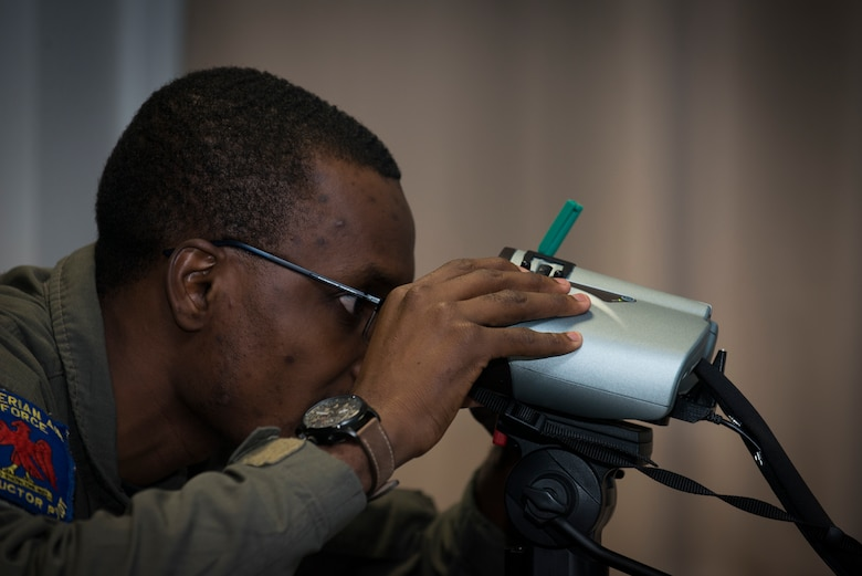 A Nigerian air force pilot peers into a set of virtual reality goggles while conducting simulator training during the 4th Combat Training Squadron's first Air to Ground Integration Course at Einsiedlerhof Air Station, Germany, Sept. 18, 2019. The course consisted of a week of classroom studies, a week of simulator training, and a capstone event where airmen controlled aircraft on a range.