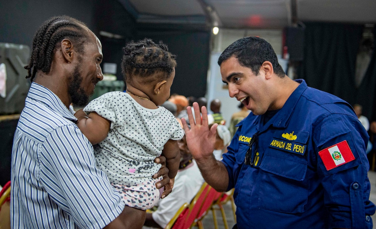 A Peruvian military member greets a Saint Lucian child