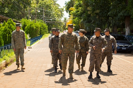 A group of military personnel walk and talk.