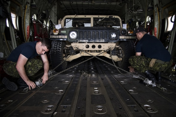Royal Canadian Air Force CC-130J Super Hercules crew members, 436 Transport Squadron, assigned to 8 Wing Trenton, Trenton, Ontario, Canada, chain down a U.S. Army humvee onto the cargo bay in preparation for the Selah Creek air base opening training scenario during Mobility Guardian 2019, Fairchild Air Force Base, Washington, Sept. 14, 2019. Exercise Mobility Guardian is Air Mobility Command's premier, large scale mobility exercise. Through robust and relevant training, Mobility Guardian improves the readiness and capabilities of Mobility Airmen to deliver rapid global mobility and builds a more lethal and ready Air Force. (U.S. Air Force photo by Tech. Sgt. Larry E. Reid Jr.)