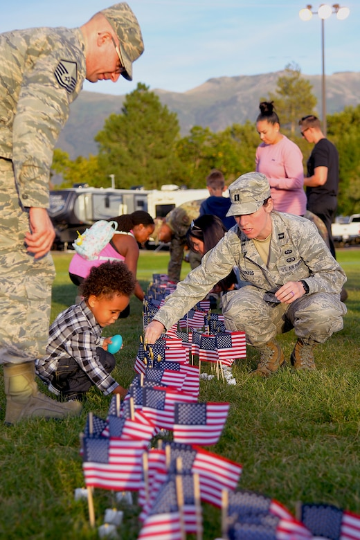 (Left to right) Master Sgt. Albert Lamboy, acting first sergeant for the 75th Logistics Readiness Squadron, his son Malachi, and Capt. Carly Lazos, 75th Air Base Wing, place candles during a Suicide Prevention Month candlelight vigil Sept. 26, 2019, at Hill Air Force Base, Utah. Throughout the day and during the vigil, Airmen placed flags in remembrance of a family member, friend or coworker who died by suicide. (U.S. Air Force Photo by Todd Cromar)