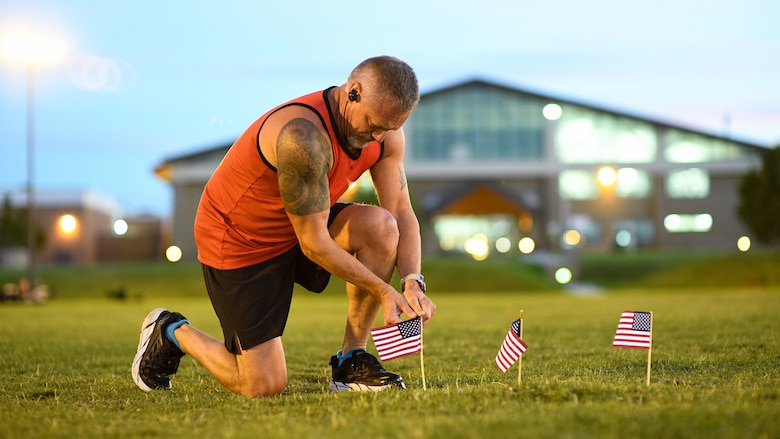 Master Sgt. Jared Barrett places a flag during a Suicide Awareness Prevnetion Month 5K ruck march/run at Hill Air Force Base, Utah, Sept. 25, 2019. Throughout the day and during the ruck march/run, Airmen placed flags in remembrance of a family member, friend or coworker who died by suicide. (U.S. Air Force photo by R. Nial Bradshaw)