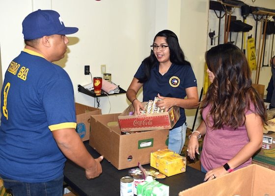 Petty Officer 2nd Class Angelica Brown (center), Navy Recruiting District San Antonio community service coordinator, volunteers at the San Antonio Food Bank Sept. 27.