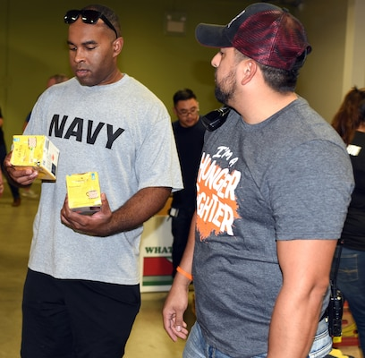 Petty Officer 1st Class Vincent Barnes (left), a leading petty officer assigned to Navy Recruiting Station North East, speaks with Mario Sanchez, a San Antonio Food Bank volunteer coordinator, regarding the expiration date on food items Sept. 27.