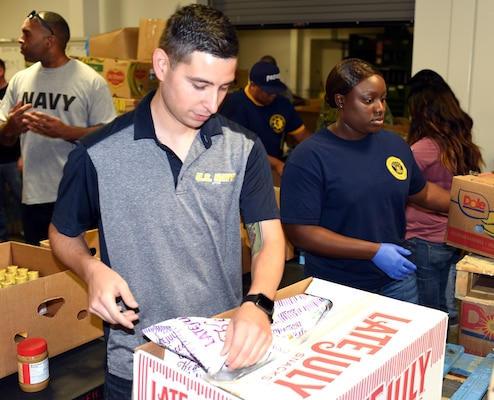 Petty Officer 1st Class Francisco Sierra (left), assigned to Navy Recruiting Station (NRS) North East, and Petty Officer 1st Class Chiemeka Jones, assigned to Navy Recruiting Station South East, volunteer at the San Antonio Food Bank Sept. 27.