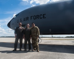 Three Airman standing in front of a KC-135 on the flight line with clouds in the background