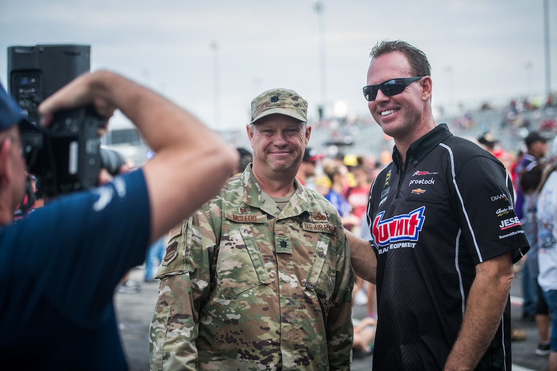 Lt. Col. William McLeod, 932nd Maintenance Group commander,  poses for a photo with a National Hot Rod Association race car driver just before the opening ceremony, Sept. 29, 2019, World Wide Technology Raceway at Gateway Motorsports Madison Illinois. McLeod was honored as a special guest for the day and presented a NHRA challenge coin. (U.S. Air Force photo by Master Sgt. Christopher Parr)