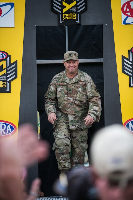 Lt. Col. William McLeod, 932nd Maintenance Group commander, enters the stage for the opening ceremony for the NHRA Midwest Nationals Sept. 29, 2019, World Wide Technology Raceway at Gateway Motorsports Madison Illinois. McLeod was honored as a special guest for the day and presented a NHRA challenge coin. (U.S. Air Force photo by Master Sgt. Christopher Parr)