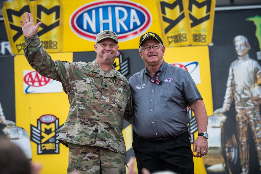 Lt. Col. William McLeod, 932nd Maintenance Group commander, waves at the crowd with Mark Adams, National Hot Rod Association Safety, Event Planning and Compliance Officer during the opening ceremony for the NHRA Midwest Nationals Sept. 29, 2019, World Wide Technology Raceway at Gateway Motorsports Madison Illinois. McLeod was honored as a special guest for the day and presented a NHRA challenge coin. (U.S. Air Force photo by Master Sgt. Christopher Parr)