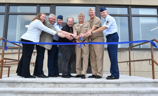 Group shot of military and civilian personnel cutting a blue ribbon in front of a building