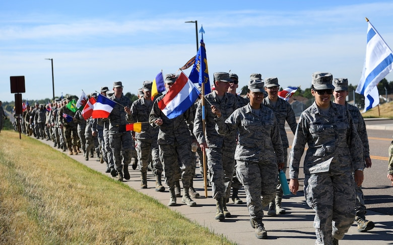 Members of Team Buckley took part in the Diversity Day march, Sept. 26, 2019, on Buckley Air Force Base, Colo. During the 1 mile march, participants held up flags from countries around the world. (U.S. Air Force photo by Senior Airman Michael D. Mathews)