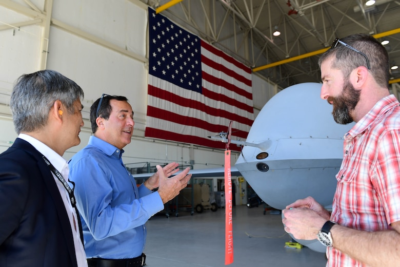 Members of the Defense Innovation Board (DIB) and Defense Digital Services (DDS) talk about the MQ-9 Reaper's capabilities at a Reaper display at Creech Air Force Base, Nevada, Sept. 12, 2019. During their visit, the DIB, DIU, and DDS members were briefed on possible changes and improvements for the highly-demanded MQ-9 platform. (U.S. Air Force photo by Senior Airman Haley Stevens)