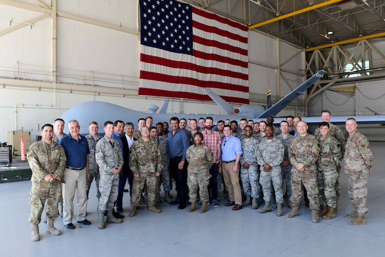 Creech Airmen and members of the Defense Innovation Board (DIB), Defense Innovation Unit (DIU) and Defense Digital Services (DDS) come together for a group photo at an MQ-9 Reaper display at Creech Air Force Base, Nevada, Sept. 12, 2019. While hosting the group, Creech Airmen showcased examples of their forward-thinking and innovative solutions within the Remotely Piloted Aircraft enterprise. (U.S. Air Force photo by Senior Airman Haley Stevens)