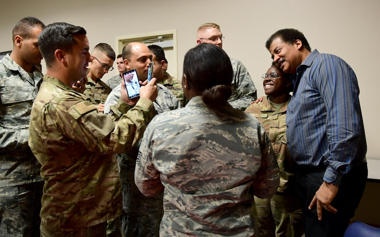 Airmen take photos with Neil Degrasse Tyson, director of the Hayden Planetarium and member of the Defense Innovation Board (DIB), at Creech Air Force Base, Nevada, Sept. 12, 2019. The DIB is made up of prominent business leaders, scholars, entrepreneurs, inventors, scientists and technologists. (U.S. Air Force photo by Senior Airman Haley Stevens)