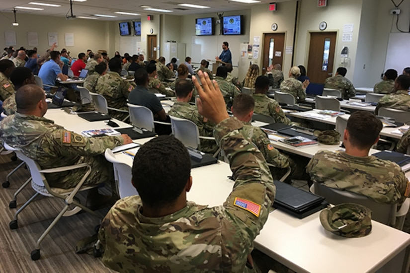 Man speaks to soldiers in a classroom setting as soldier in foreground raises hand to ask a question.