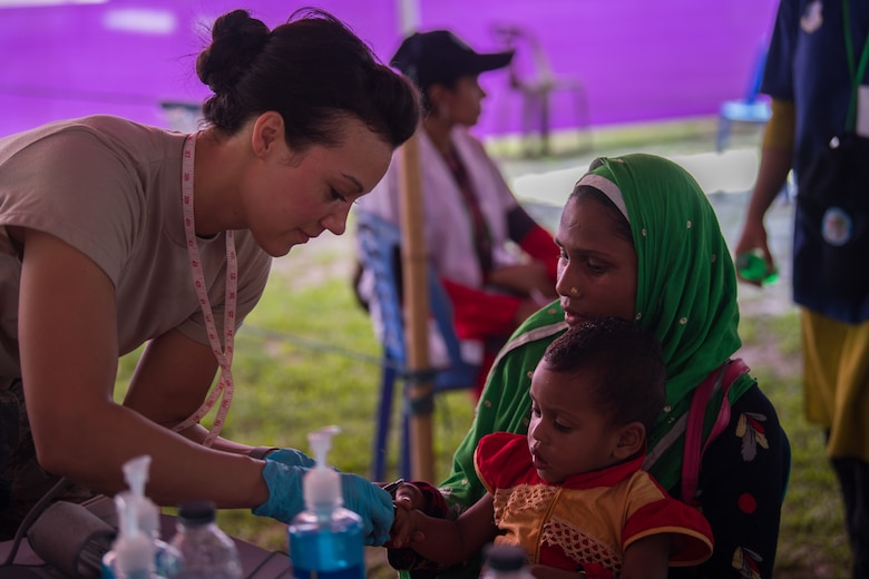 U.S. Air Force Tech. Sgt. Stephanie Blake, 354th Medical Group paramedic, Eielson Air Force Base, Alaska, checks vitals for a Bangladeshi child during Pacific Angel 19-1 in Lalmonirhat, Bangladesh, June 23, 2019. The United States developed Pacific Angel to demonstrate the Department of Defense goodwill through global medical outreach and enhancing regional partnerships through humanitarian assistance and disaster relief missions to include medical, dental, optical, engineering assistance and subject matter expert exchanges alongside host-nation service members and regional allies and partners. (U.S. Air Force photo by Staff Sgt. Ramon A. Adelan)