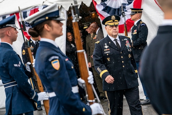 Army Gen. Mark A. Milley walks past honor guard troops on a rainy field.