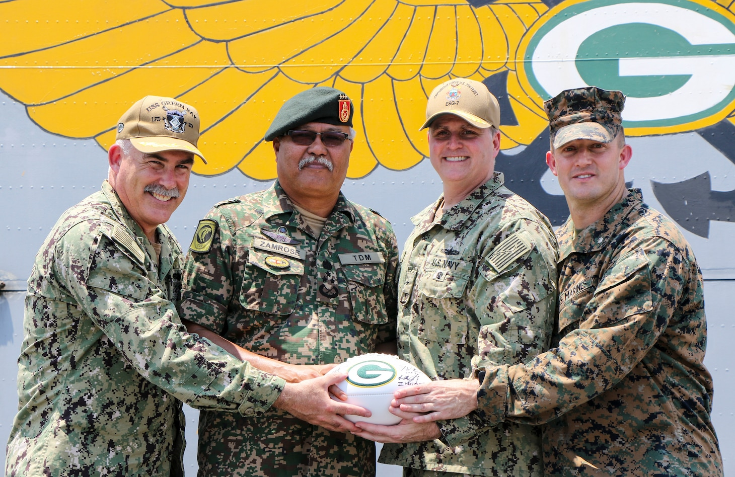 CELEBES SEA (Sept. 30, 2019) Captain Michael Harris, commanding officer of the amphibious transport dock ship USS Green Bay (LPD 20), Malaysian Armed Forces (MAF) Lt. Gen. Dato' Wira Zambrose bin Mohd Zain, Army Field Eastern Commander, Rear Adm. Fred Kacher, commander of Expeditionary Strike Group 7, and Lt. Col. William Jacobs, commander of troops, 3rd Marine Division, pose for a photo with a Green Bay Packers football given as a memento during an opening ceremony for exercise Tiger Strike 2019. Tiger Strike focuses on strengthening combined U.S. and Malaysian military interoperability and increasing combat readiness through amphibious operations and cultural exchanges between the MAF and the U.S. Navy, Marine Corps team.