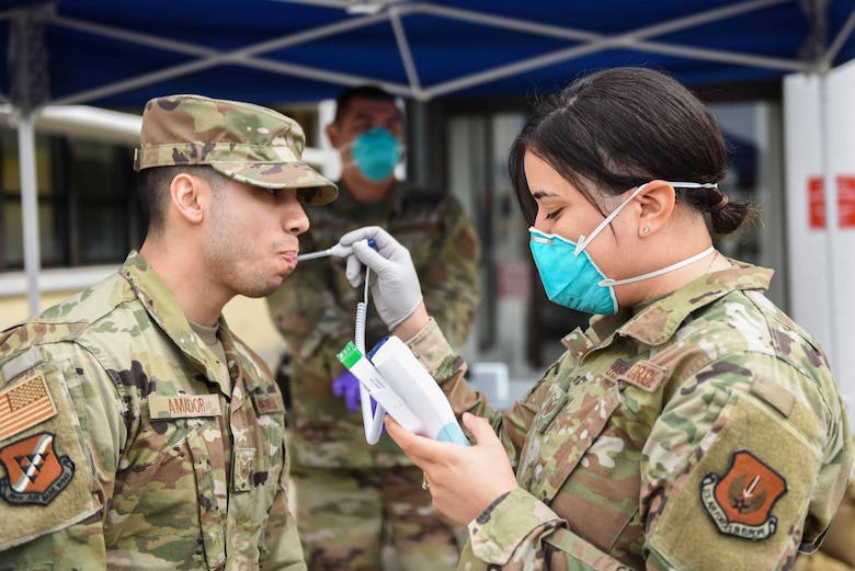 U.S. Air Force Staff Sgt. Melissa Lozada, 39th Medical Support Squadron resource management office non-commissioned officer in charge, right, checks a visitor's temperature, March 20, 2020, at Incirlik Air Base, Turkey. In response to the COVID-19 pandemic, the 39th Medical Group has altered its operations to focus on acute care cases. (U.S. Air Force photo by Staff Sgt. Joshua Magbanua)