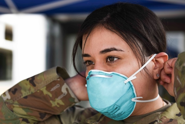 U.S. Air Force Staff Sgt. Melissa Lozada, 39th Medical Support Squadron resource management office non-commissioned officer in charge, dons a protective mask prior to screening visitors at the 39th Medical Group, March 20, 2020, at Incirlik Air Base, Turkey. Military and civilian officials at the 39th Air Base Wing are taking steps to curb the potential spread of the Coronavirus at Incirlik. (U.S. Air Force photo by Staff Sgt. Joshua Magbanua)