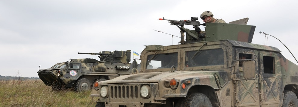 A firing squad from 1st Battalion, 26th Infantry Regiment, 2nd Brigade, 101st Airborne Infantry Division (Air Assault), in a High Mobility Multi-Wheeled Vehicle right, and a Ukrainian armored military vehicle from the 10th Mountain Assault Brigade prepares to engage targets during a defensive maneuvers during Rapid Trident 2019 in Yavoriv, Ukraine, Sept. 26, 2019. The meeting is to discuss the first ever brigade sized element joint mounted defensive maneuver live fire exercise performed by the U.S. and the Armed Forces of Ukraine, which demonstrates the defensive capabilities of the multi-national force to build a stronger and more unified Europe. (U.S. Army photo by Sgt. Kyle Larsen.)