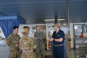 Capt. Scott Hattaway, right, commanding officer of the expeditionary mobile base platform ship USS Lewis B. Puller (ESB 3), speaks to a US. Army air weapons team during a guided tour by Capt. Peter Mirisola, center, commodore of Combined Task Force (CTF) 55. Puller is deployed to the U.S. 5th Fleet area of operations in support of naval operations to ensure maritime stability and security in the Central Region, connecting the Mediterranean and the Pacific through the western Indian Ocean and three strategic choke points.