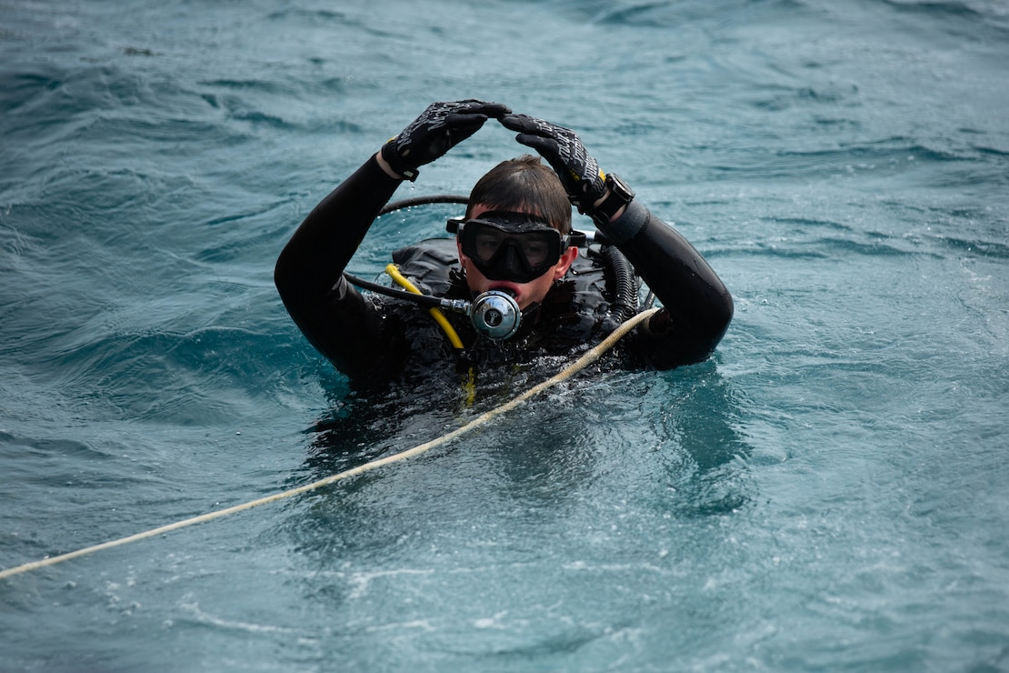U.S. Marine signals to the diving supervisor during open-circuit dive training at Naval Base White Beach, Okinawa, Japan, Mar. 30.
