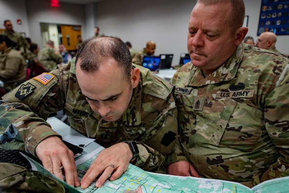 Capt. Cody Myers and 1st Sgt. Timothy Horner, 128th Brigade Support Battalion, use a map to plan out logistical support locations for an upcoming exercise during the National Guard Bureau's Northern Strike Exercise Planning Conference at the Pittsburgh International Airport Air Reserve Station, Feb. 11, 2020.