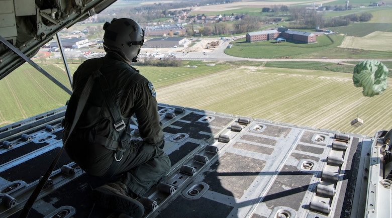 Tech. Sgt. Alex Carlson, 37th Airlift Squadron loadmasters, push an airdrop package out over Chievres Air Base, Belgium, March 26, 2020.