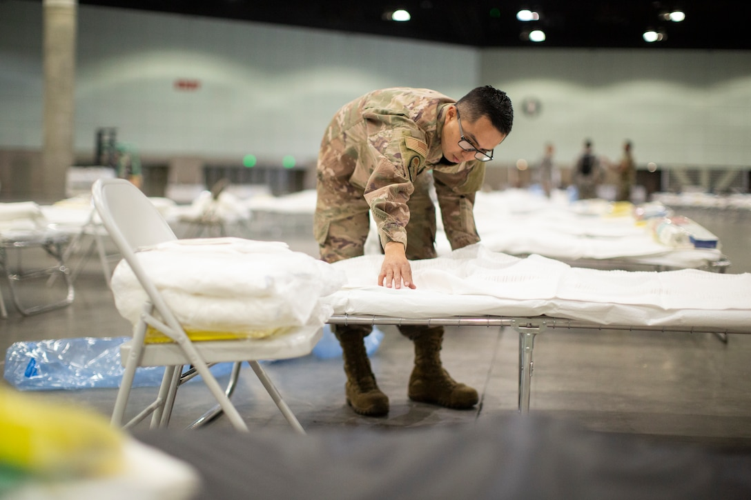 A male airman puts sheets on a  makeshift bed.