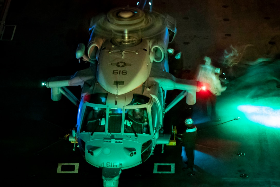 Sailors put fuel in a helicopter that is lit up at night.