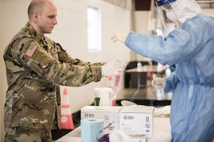 Soldier and Airman bagging COVID-19 test.