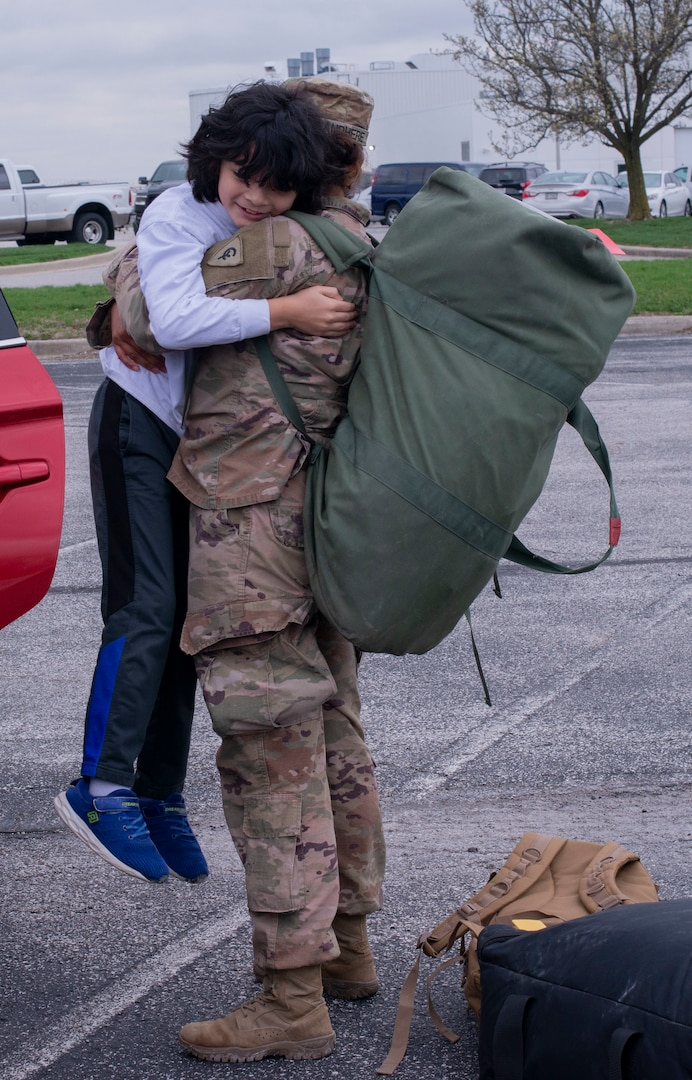 An Indiana National Guard Soldier with the 38th Infantry Division embraces her loved one in Indianapolis, March 31, 2020, after being deployed for nine months in the Middle East and spending two weeks in quarantine at Fort Hood, Texas. Despite having a non-traditional homecoming to adhere to social distancing standards Soldiers were still able to greet their families.