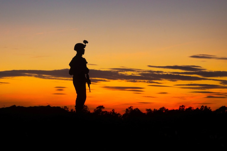 A Marine, shown in silhouette, stands in a field with an orange cloud-streaked sky behind him.