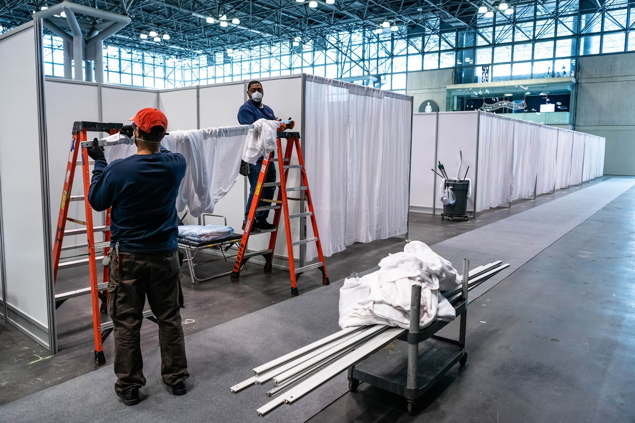 Two men set up partitions and curtains on a large convention center floor.