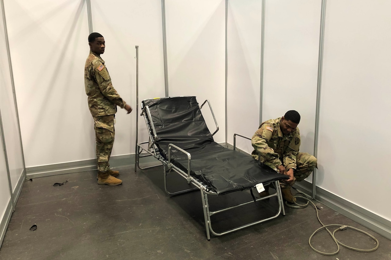 Two service members set up a cot.