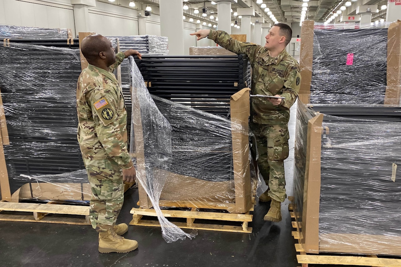 Two service members unwrap material on a shipping pallet.