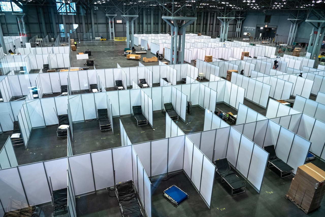 Dozens of partitions and cots are set up on a large convention center floor.