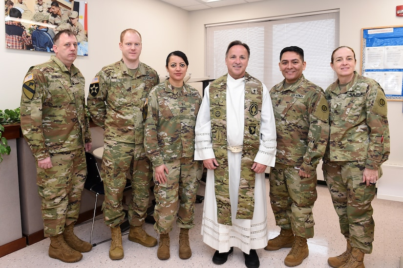 Father Matt Foley, fourth from the left, parish pastor for St. James Catholic Church, in Arlington Heights, Illinois, pauses for a photo with local Soldiers, assigned to the 85th U.S. Army Reserve Support Command, during the unit's battle assembly weekend training, February 9, 2020.