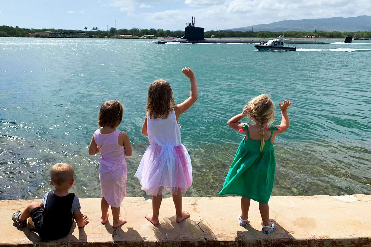 Four children look toward a submarine; two wave.