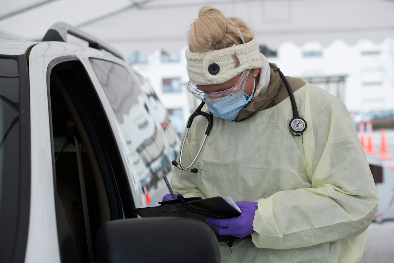 An airman dressed in personal protective equipment writes down medical information.